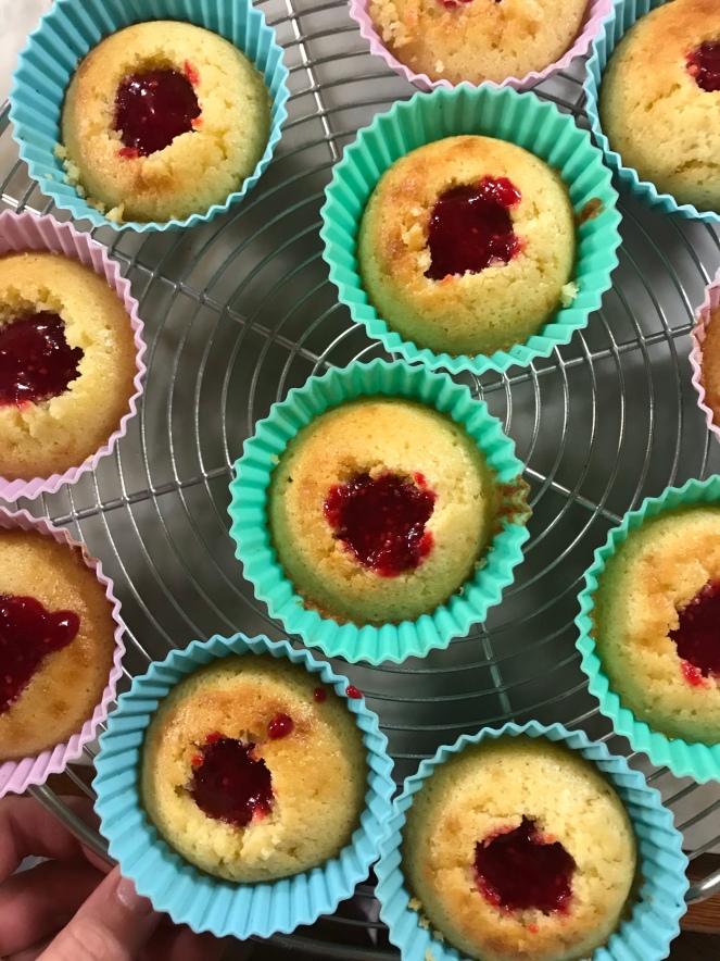 Les cupcakes creusés sont garnis de confit de framboises.