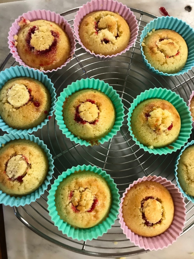 Les cupcakes garnis de confit de framboises sont refermés avec le chapeau creusé.