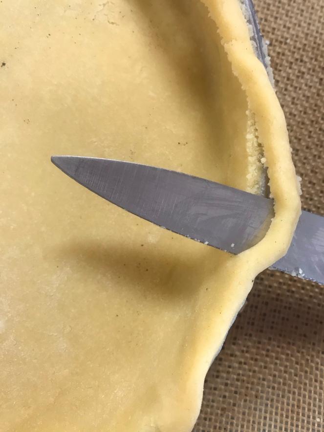 Avec un couteau d'office, coupez l'excédent de pâte qui dépasse du cercle à tarte.